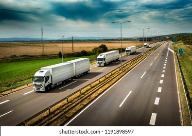 Caravan or convoy of White Lorry  trucks in line on a country highway