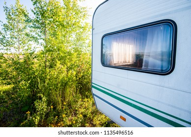 A caravan near the lake and the green forest on a sunny day, close-up, Latvia