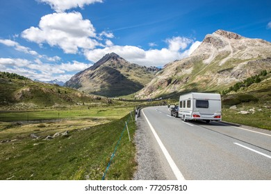A caravan on the way to the vacations. Swiss mountains with a cloudy sky