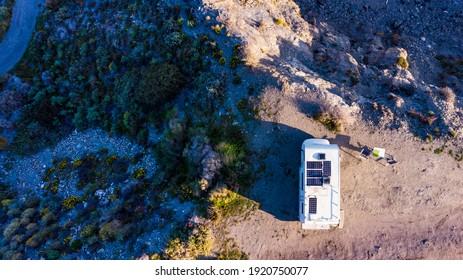 Caravan with solar panels on roof camping on cliff sea shore. Mediterranean region of Villaricos, Almeria, eastern Andalusia, Spain.