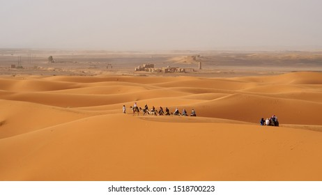 Caravan of tourists riding camels during Sahara desert tour. Background with ancient ruins. Located in Merzouga, Morocco.