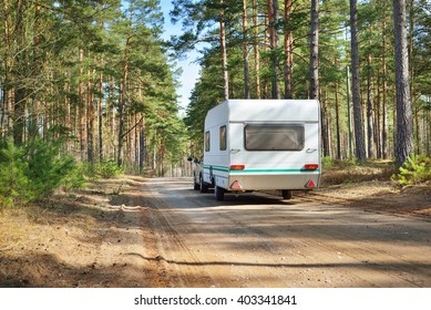 Caravan trailer on a forest road, on a sunny spring day