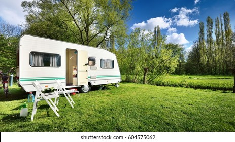 Caravan trailer on a green lawn, on a sunny spring day