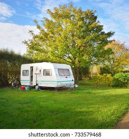 Caravan trailer on a green lawn under the trees in camping, on a sunny Autumn day in France