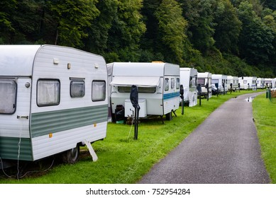 Caravans or camper trailers set on the river side of river Semois in camp site or camping in Ardennes region of Wallonia in Belgium.
