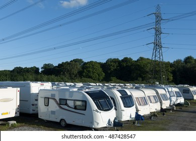 Caravans stored in rows on a sunny day.
