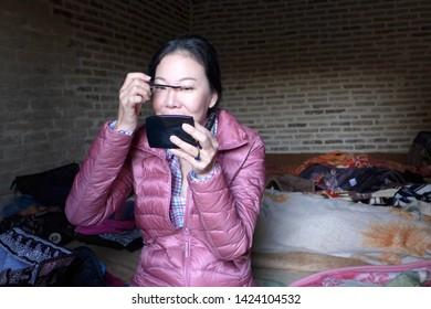 Caravanserai, Kashan, Iran - October 2017 : An asian tourist applying make up in the morning inside a caravanserai near Kashan in Iran.