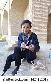 Caravanserai, Kashan, Iran - October 2017 : An elderly asian tourist having a snack at a caravanserai near Kashan in Iran.