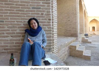 Caravanserai, Kashan, Iran - October 2017 : A young female asian tourist sitting against the brick wall writing a diary at a caravanserai near Kashan, Iran.