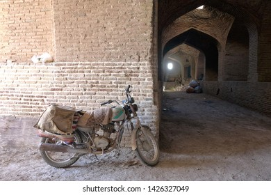 Caravanserai, Kashan, Iran - October 2017 : A vintage motorcycle parking at a caravanserai near Kashan, Iran.