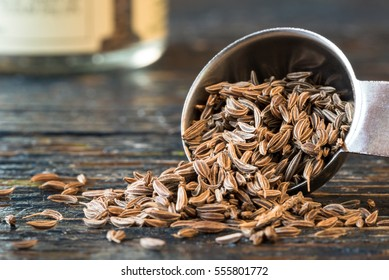Caraway seeds spilling from a measuring spoon