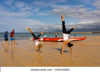Carbis Bay, St Ives, Penzance, Cornwall - England - 31st August 2018 - A mother and daughter having fun on the beach together doing cartwheels and gymnastics