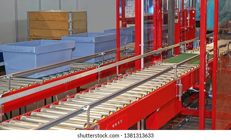 Carboard box at conveyor rollers in factory