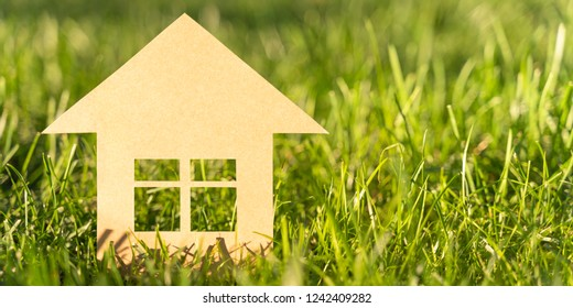 Carboard family house on a grass lawn sunny day