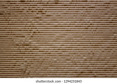 CARBOARD TEXTURE SHOWING THE CORRUGATED INTERIOR OF A PIECE OF CARDBOARD