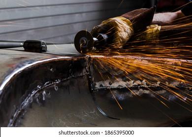 Rénovation de carrosserie, étincelle, soudure et coupe-métal. Homme travaillant avec des outils industriels pour la rénovation de carrosserie.