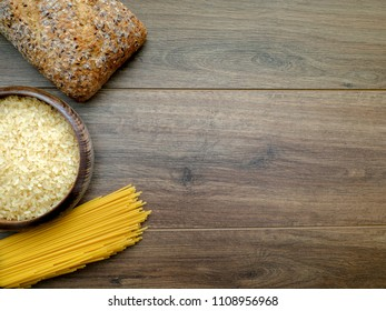 Carbohydrates (spaghetti, bread and rice) on the dark wooden background with copy space for text, top view.