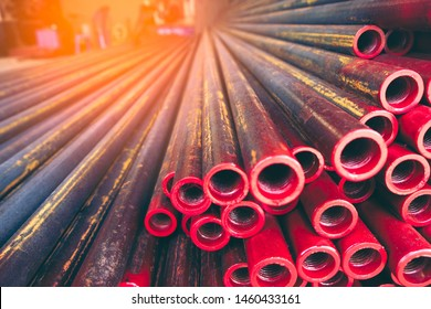 CARBON or GALVANIZED STEEL PIPES, one side is red color with spiral, beautifully arranged wait for some construction, organize like stack in the outdoor storage room at the construction site, Thailand