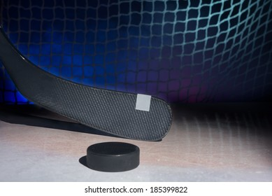 Carbon hockey stick on ice, against smoky background