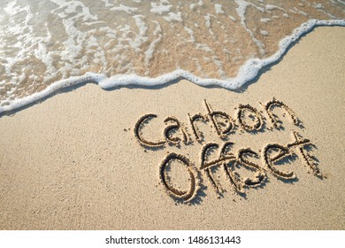 Carbon Offset eco-friendly message handwritten on smooth sand beach with incoming wave