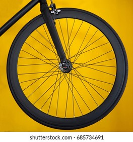 Carbon wheel for road bicycle on yellow background. Black wide rim and thin tyre.