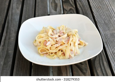 Carbonara pasta dish on a white plate.