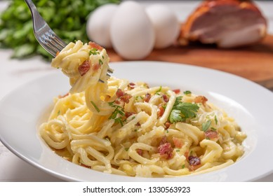 Carbonara pasta with pancetta, egg, hard parmesan cheese and cream sauce.  White plate on white wooden background. Soft light, angle view. Traditional italian cuisine. Pasta alla carbonara