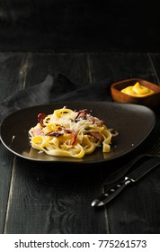 Carbonara paste with Parmesan cheese and sauce on a plate on a dark background