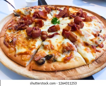 Carbonara Pizza with Smoked bacon, Ham, Mushroom, Cherry Tomato, Egg, Cheese and Cream Sauce that was placed on the wooden dish. This is a popular Italian cuisine. For a special meal