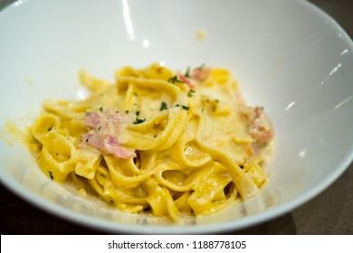 Carbonara in the white bowl. Carbonara pasta, spaghetti with pasta egg, parmesan cheese and cream sauce. Carbonara spaghetti served in the restaurant.