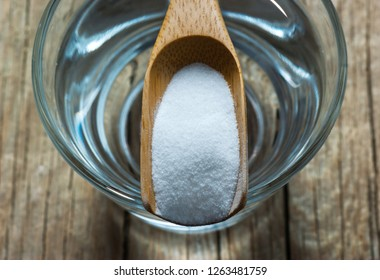 Carbonate powder or baking soda and glass of water on wooden table, alternative medicine, organic cleaner