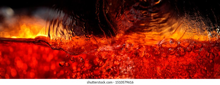 Carbonated drink on a dark background, abstract splashing. Macro shot.
