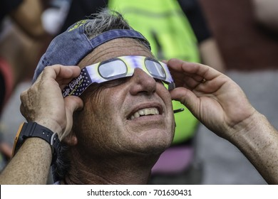 CARBONDALE, IL/USA - AUGUST 21, 2017: A man holds eclipse glasses to protect his eyesight as he watches the Moon hide the Sun before totality during the Great American Eclipse.