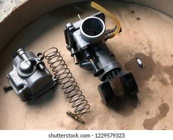 Carburetor of Motorcycle engine was separated into parts for repair on brown paper, in dark tone. Repairing machine. Selective focus.