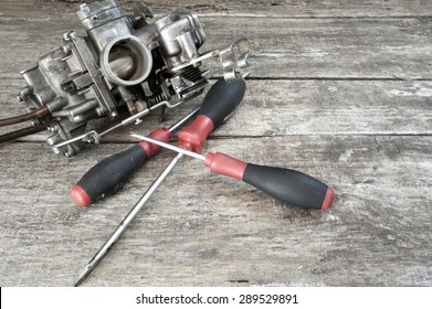 Carburetor and screwdrivers on wooden surface