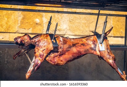 The carcass of a lamb is roasted on a spit. Close-up carcass of a sheep that is roasting on the spit.