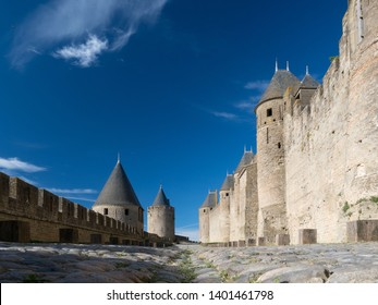 Carcassonne, Aude / France - May 16, 2019:A low angle view shows cobbled paving at Carcassonne citadel with the walls, towers leading into distance with a perfect blue sky