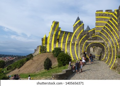 CARCASSONNE, FRANCE - 07-28-2018: Installation art by italian artist Felice Varini in the Castle of Carcassonne. Fortified medieval city, UNESCO. Yellow circles.
