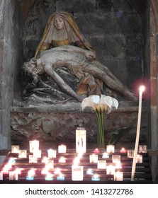Carcassonne, France - April 15, 2017: statue of body of Jesus Christ resting on the lap of Virgin Mary after the Crucifixion with many glowing candles in the foreground and dark church ambiance