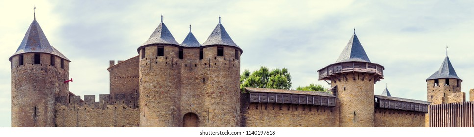 CARCASSONNE, FRANCE - JULY 22, 2017: Ancient fortress Carcassonne - view of the walls and towers, wide angle panorama. Medieval castles and historical landmarks of France, Languedoc-Roussillon region.