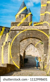 Carcassonne, France - June 15th, 2018: Young woman performs a ballerina move at the cobbled entrance to walled fortress, UNESCO World Heritage Site, artwork by Felice Varini 20 year anniversary UNESCO