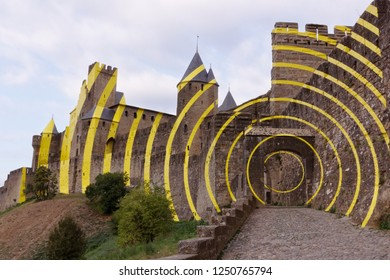 """Carcassonne, France - June 2018: Swiss artist Felice Varini has created """"Concentric, eccentric"""" yellow circles on the historic fortress of Carcassonne."""