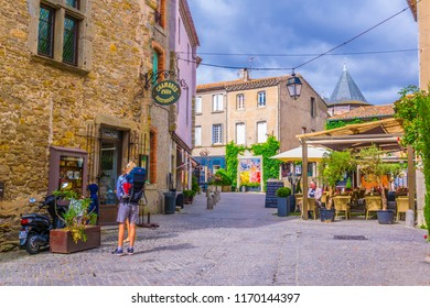 CARCASSONNE, FRANCE, JUNE 28, 2017: People are strolling through an alley in the old town of Carcassonne, France