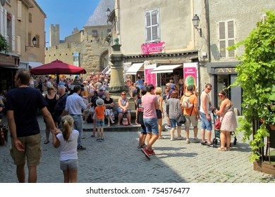Carcassonne, Languedoc-Roussillon, France - August 24 2017: Tourists relaxing in the sunshine along a cobbled street in the medieval French fortified city of Carcassonne, La Cite