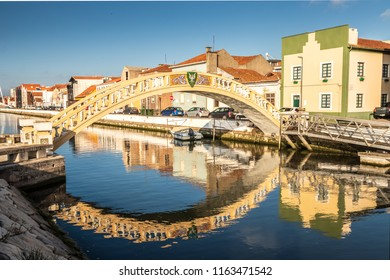 Carcavelos bridge on the São Roque canal, in the city of Aveiro, Portugal, with houses in the background and reflection in the water.