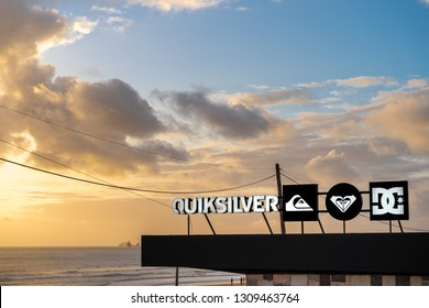 Carcavelos, Portugal - 12/27/18: Quiksilver brand at carcavelos beach. High contrast logo. Sunset, ocean waves, boat, surfers in the background.