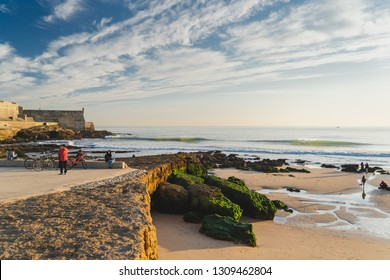 Carcavelos, Portugal - 12/31/18: Carcavelos beach and Saint Julian fortress. People enjoying the warm december sunset , small waves, rocks covered in green moss.