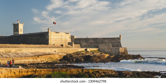 Carcavelos, Portugal - 12/31/18: Saint Julian Fortress with lighthouse tower, beach (praia) of Carcavelos,Ocean waves from the Atlantic, eroded beach rocks.