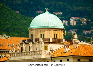 Carciotti palace, Trieste, Italy. The dome and part of the facade. Close-up photo of the historical building of XVIII century with hills in background.