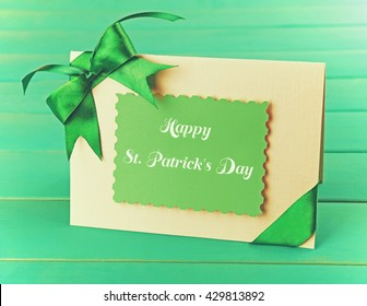 Card decorated with green bow on wooden background. Happy St. Patrick's Day